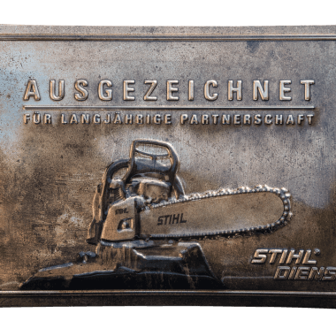 Embossed tin metal sign for Stihl, 60 cm x 40 cm in three metallic versions; this is bronze